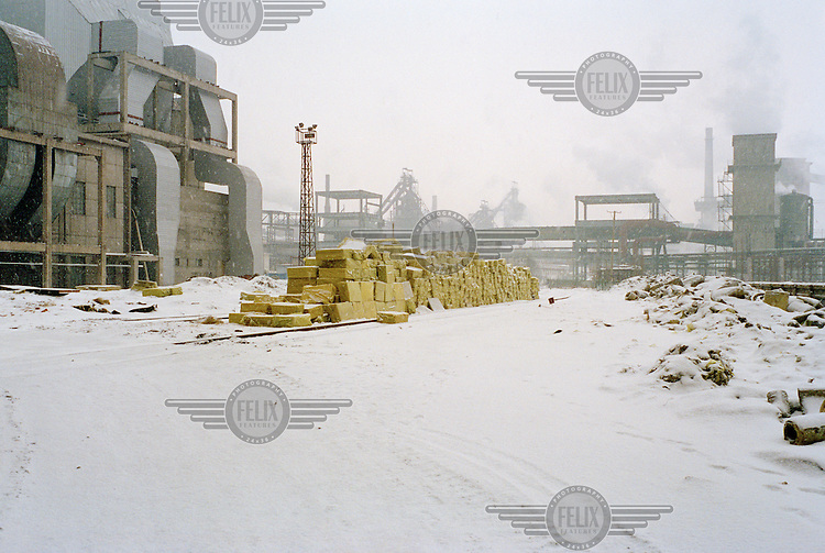 New packs of insulation lie on a railway track next to the construction site of a new coal -fired power station. Emissions from a nearby steel plant can be seen in the distance. China is in the process of building over 500 new coal power plants to meet the increasing energy demand.
