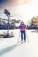 Smiling female ice skating - skridskoåkning on a frozen lake in Svartedalen, South Bohuslän, West Sweden, Sweden - Västsverige, Sverige