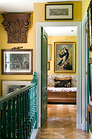 A dark green balustrade leads to a guest room where a Murillo inspired copy of the Madonna hangs above a traditional wooden day bed with a floral pattern cushion