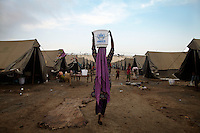 A woman carries a bucket of clean water on her head at an IDP (internally displaced persons) camp set up by UNHCR (United Nations High Commission for Refugees) for those affected by the flooding. Severe flooding had left at least 1,600 people dead and affected up to 20 million.