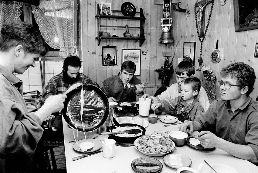 Switzerland. Canton Nidwald. Oberalp. 1500 meters high. Engelberg valley. At supper in the evening, the family Arnold eats melted cheese on a loaf of bread, bacon and pasta. Three brothers and and a young nephew. Swiss alpine farmers. Alps mountains peasants. © 1997 Didier Ruef