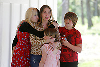 Erica Kelso, receives hugs from her daughters Maggie, 14, Sophie, 7, and son Louie, 10, Friday, April 30, 2021, as she speaks in the carport during a celebration for the completion of her Realtor Build Habitat for Humanity of Washington County home in Fayetteville. Kelso put in more than 300 hours of sweat equity and will pay a monthly affordable mortgage. This is the 57 Habitat for Humanity of Washington County house built in the county since 1991. Check out nwaonline.com/210501Daily/ and nwadg.com/photos for a photo gallery.<br /> (NWA Democrat-Gazette/David Gottschalk)
