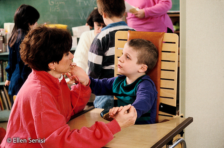 MR / Schenectady, NY.Yates Arts Magnet School / Special Education Class.Teacher calms boy (7, autistic, ADHD) after outburst. Boy sits in special chair where he can be restrained if he loses self control. .MR: Mon1, Cou3.PN#:15838                        FC#:21604-00120.scan from slide.©Ellen B. Senisi