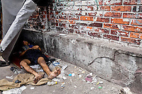 A Colombian drug addict lies on the street in the slum of Calvario, Cali, Colombia, 5 April 2004. Calvario, a slum right in the centre of the city, is considered the social bottom of Cali society. Poor dwellers recollect the garbage in the near city centre to sell it for recycling, while their children get high by sniffing the shoe glue on the dirty streets of ghetto. The order in Calvario is maintained by the illegal authorities, usually former policemen or army members, who set their own rules. Criminality, drug abuse, unemployment never allow the slum people jump off the misery and stop being the second category citizen within the rigid society of Colombia. Although Christian missionary organizations attempt to provide help, the overall situation does not improve.