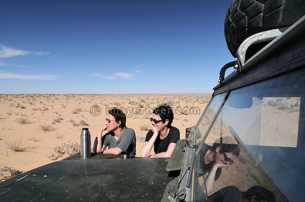 Africa, Tunisia, nr. Douz. Desert travellers Kerstin and Doris having a cup of tea on the bonnet of their historic 1962 Land Rover Series 2a.  --- No releases available, but releases may not be needed for certain uses. Automotive trademarks are the property of the trademark holder, authorization may be needed for some uses.  --- Info: Image belongs to a series of photographs taken on a journey to southern Tunisia in North Africa in October 2010. The trip was undertaken by 10 people driving 5 historic Series Land Rover vehicles from the 1960's and 1970's. Most of the journey's time was spent in the Sahara desert, especially in the area around Douz, Tembaine, Ksar Ghilane on the eastern edge of the Grand Erg Oriental.