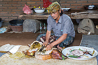 Bali, Indonesia.  Roasted Pig Being Cut up by Village Cook.  He is wearing the udeng, the traditional Balinese head cloth.