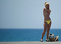 A woman in topless puts suncream on her body