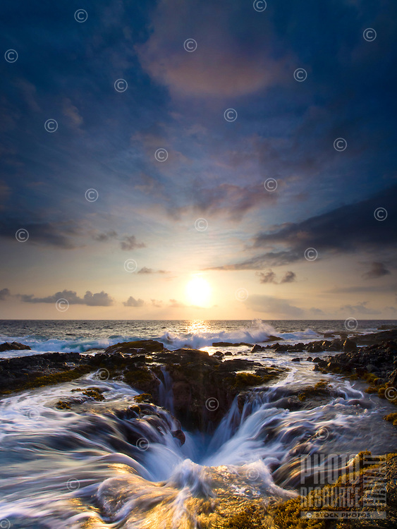 The cloudy sky opens up to reveal an amazing sunset while the raging surf drains into a hole along the Keahole Point shoreline, Big Island.