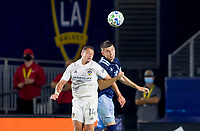 """CARSON, CA - OCTOBER 18: Javier """"Chicharito"""" Hernandez #14 of the Los Angeles Galaxy battles with Ranko Veselinovic #4 of the Vancouver Whitecaps   for a ball in the air during a game between Vancouver Whitecaps and Los Angeles Galaxy at Dignity Heath Sports Park on October 18, 2020 in Carson, California."""