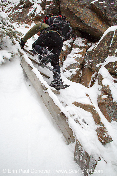 Franconia Notch State Park - Winter hiker on snow-covered trail ladder along the Hi-Cannon Trail in the White Mountains, New Hampshire USA during the winter months.