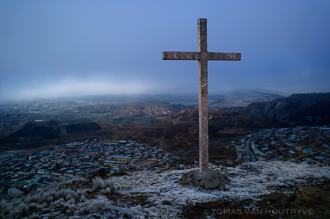 A view of the Paragsha neighborhood of Cerro de Pasco and mine tailings are seen from a nearby hill with a cross on Aug. 5, 2012.