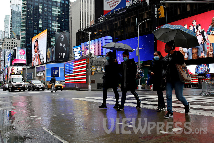 NEW YORK - NEW YORK - MARCH 24: People walk under the rain at Times Square on March 24, 2021 in New York. With more people every day getting vaccinated transmission rates are dropping, arts an entertainment values should open at 33% capacity on April 2, as outdoor amusement parks will open at 25% capacity one week later (Photo by John Smith/VIEWpress)