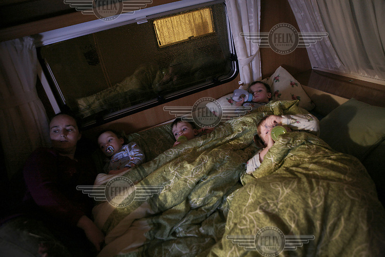 Jean Sheridan puts her triplets and daughter Viviana to bed in their trailer at Dale Farm, an Irish Travellers' site on a former scrapyard in Essex.