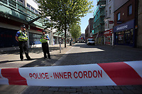 Pictured: Police at the junction of Union and Oxford Street in Swansea city centre with the entrance to the Quadrant in the background Wednesday 24 May 2017<br />Re: The Quadrant shopping centre in Swansea has been evacuated following reports of a suspicious package being found.<br />The bus station and Swansea Indoor Market have also been closed as part of the evacuation.