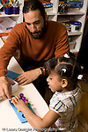 Preschool Headstart 3-5 year olds young male teacher working with girl on counting and peg activity vertical