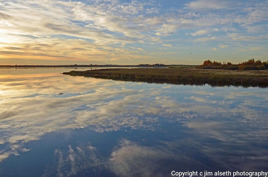 Clouds reflect on the glassy calm waters of Big Lake Alberta in the fall...