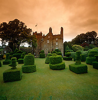 Individual topiary hedges are placed like chess pieces on the manicured lawns at Earlshall Castle in Scotland