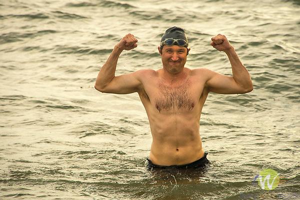 Hammonasset Beach State Park, Madison, CT. Man expressing strength in ocean.