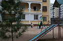Uzbekistan - Tashkent - Mother and daughters sitting in the playground of their house in Sergeli, the largest working class neighborhood of the capital.