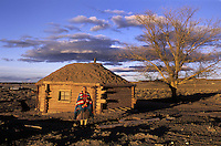 Jennie, Navaho woman in front of her hogan   <br /> Nazlini Navaho Reservation, Arizona.<br /> Jennie lives on the remote reservation with her family in a traditional mud hogan with no running water or electricity. With the onset of winter approaching they have only a small wood-burning stove for warmth. Work is scarce and Jennie is worried for the future of her niece.