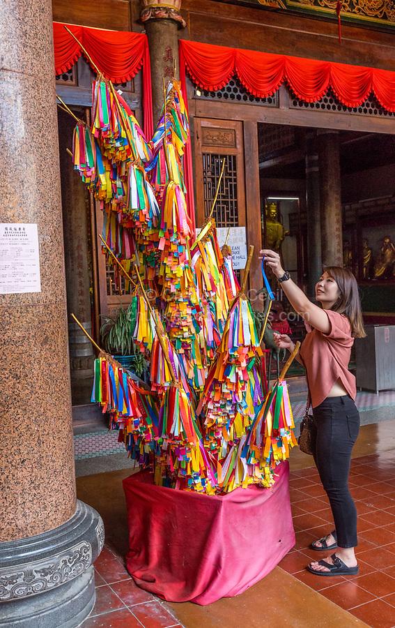 Young Woman Hanging a Wishing Ribbon on the Wishing Tree, Kek Lok Si Buddhist Temple, George Town, Penang, Malaysia.