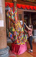 Young Woman Hanging a Wishing Ribbon on the Wishing Tree, Kek Lok Si Buddhist Temple, George Town, Penang, Malaysia.