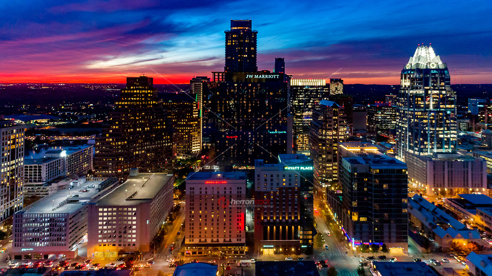 A gorgeous fiery sunset engulfs the sky over the downtown Austin Skyline — hotel row showcasing Austin's hotel and financial district.