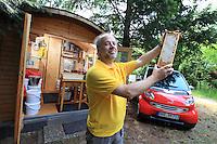 """Ralf Schneider Rathmann, 50 ans, possède quarante ruches dans  Berlin. Ce passionné pose devant son rucher principal installé dans le cimetière de Luisen-Friedhof dans le quartier de Charlottenburg-Wilmersdorf.<br /> Dans le fond à gauche, la cabane d'extraction de Ralf ou toutes les machines fonctionnent à l'énergie solaire. A droit, la Smart de Ralf est dédié à l'apiculture.  """"Berlin est un très bon endroit pour l'apiculture"""" nous déclare ce plombier de métier. Je produit près de 6 miels monoifloraux différent que je vends avec ma femme sur les marchés du week-end""""./// Ralf Schneider Rathmann, 50 years old, owns forty hives in Berlin. This enthusiast is posing here in front of his main apiary set up in the Luisen-Friedhof cemetery in the Charlottenburg-Wilmersdorf neighborhood. In the background on the left is Ralf's extraction cabin where all the machines work on solar energy. To the right, Ralf's Smart car is devoted to beekeeping. """"Berlin is a very good place for beekeeping"""", this plumber by profession tells us. """"I produce nearly 6 different monofloral honeys that I sell with my wife in the markets on weekends."""""""