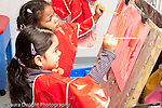 Education preschool 3-4 year olds art activity two girls sharing easel while painting using opposite hands (holding brush in right or left hand)