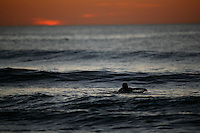 A surfer paddles out into the waves after sunset. Grand Plage beach, Biarritz, France.