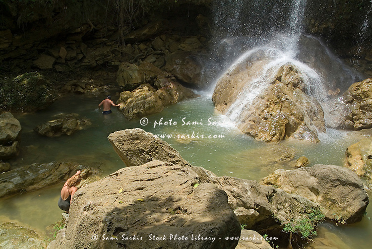 Man and woman climbing rocks and swimming at the foot of a waterfall, Soroa Cascade, Cuba.