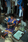 A money changer waits at a foot path with coins .She charges Rs 5 to change a Rs. 100.00 note to coins. Kolkata, West Bengal,  India  7/18/2007.  Arindam Mukherjee/Landov