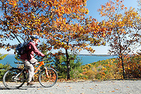 Woman mountain biking on historic gravel carriage road, Mount Desert Island, Acadia National Park, near Bar Harbor, Maine, USA