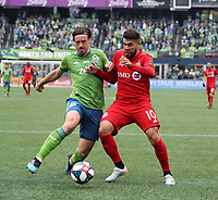 SEATTLE, WA - NOVEMBER 10: Gustav Svensson #4 of the Seattle Sounders FC and Alejandro Pozuelo #10 of Toronto FC challenge for the ball during a game between Toronto FC and Seattle Sounders FC at CenturyLink Field on November 10, 2019 in Seattle, Washington.
