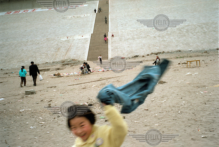 Recently arrived settlers visit the river banks by the newly built docks.  Land here has been reclaimed and the docks built to accommodate the imminent rise in the Yangtze river's water level after the completion of the Three Gorges Dam project.