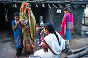 The local health worker, Shabjaan Fakira Wadhey (centre, sitting) sips her tea while Rekha RAMESH's mother and younger siblings look on  house in Dhawati VIllage of Khaknar block of Burhanpur district in Madhya Pradesh, India.  Photo: Sanjit Das/Panos for ACF