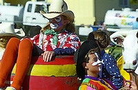 Three children rest at the annual Fourth of July Makawao Rodeo Parade in the upcountry town of Makawao. Maui's cowboy or paniolo town got it's start in the early 1800s as a support community for the upcountry cattle ranches. Today you can still see the old hitching posts.