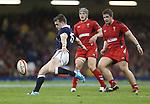 Scotland full back Stuart Hogg kicks under pressure from Wales pair Jonathan Davies and Rhodri Jones.<br /> RBS 6 Nations 2014<br /> Wales v Scotland<br /> Millennium Stadium<br /> <br /> 15.03.14<br /> <br /> ©Steve Pope-SPORTINGWALES