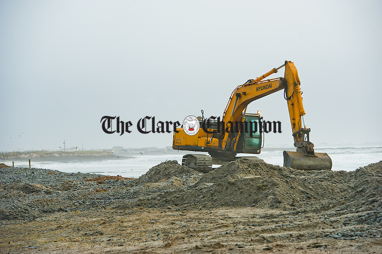 An excavator working on the flood defence at Seafield in Quilty ahead of the high tides expected in the coming days as part of the Clare County Council's reaction to the recent storm and flood damage in the area. Photograph by John Kelly.