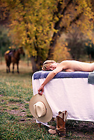 Cowgirl relaxes on massage table at a dude ranch & spa.