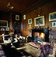 The walls of the 'smoking' room are decorated with black and white Highland scenes and Macpherson tartan rugs are used as chair covers