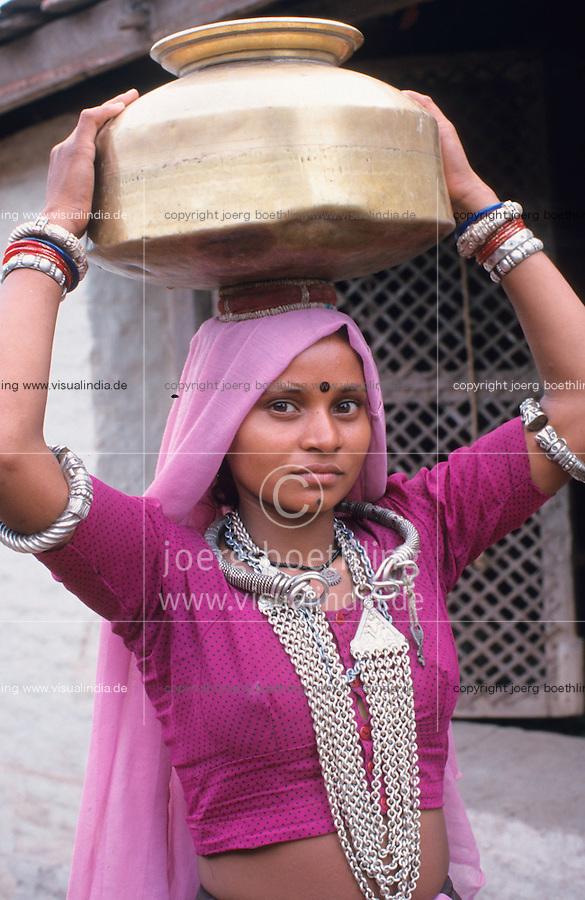 INDIA Dhar, Adivasi woman carry brass pot with water on the head / INDIEN Dhar Adivasi Frau traegt Trinkwasser in einem Messing Krug auf dem Kopf