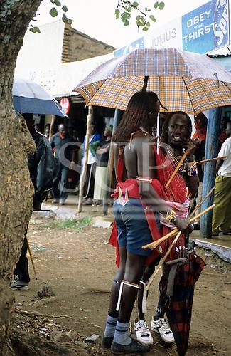 Lolgorian, Kenya. Two Maasai moran with umbrella outside shops in the town.