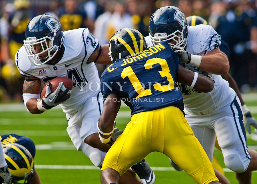 Connecticut tailback D.J. Shoemate (24) takes a block by running back Anthony Sherman, right, on Michigan safety Carvin Johnson (13), in the second quarter of an NCAA college football game, Saturday, Sept. 4, 2010, in Ann Arbor. Michigan won 30-10. (AP Photo/Tony Ding)
