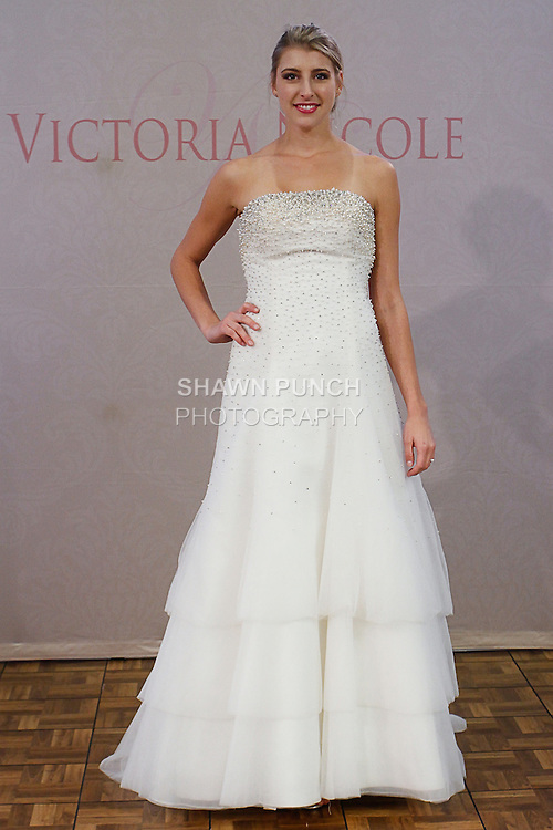 Model poses in a Style 1202 bridal gown from the Victoria Nicole Spring 2014 collection by Victoria McMillan, during Couture Bridal Fashion Week, on October 13, 2013.