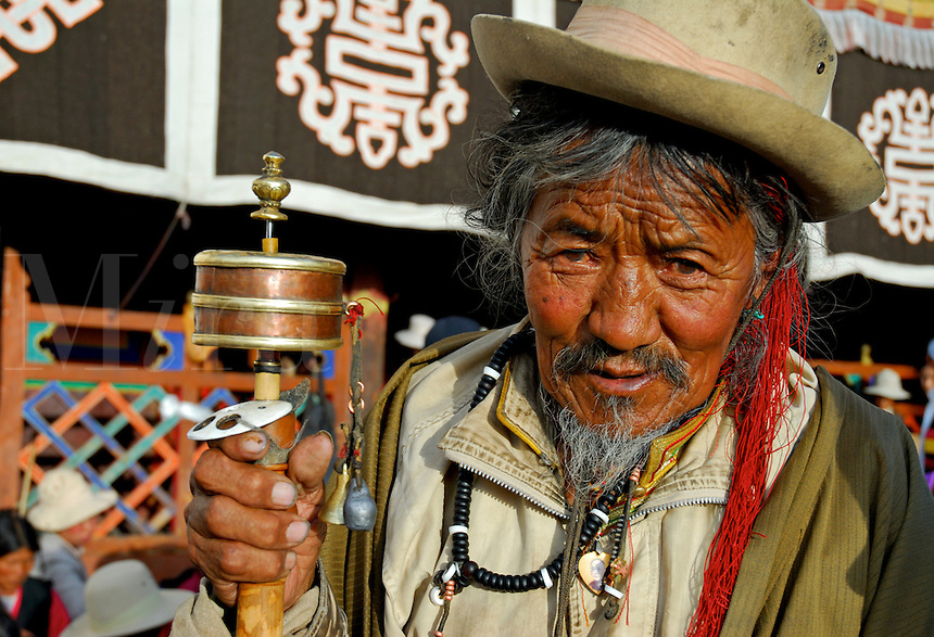 Tibetan Buddhist pilgrim with prayer wheel and mala beads outside the Jokhang Temple during Saga Dawa festival, Lhasa, Tibet.