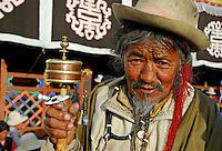 Tibetan Buddhist pilgrim with prayer wheel and mala beads outside the Jokhang Temple during Saga Dawa festival, Lhasa, Tibet.