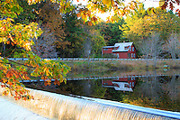 Fall colors of the leaves on the tall trees is seen along with a red house reflected in a pond with a small waterfall in the foreground during the New England Fall season.