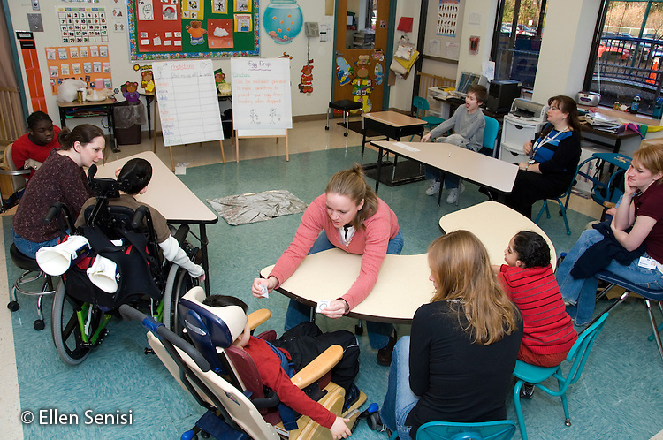 MR / Albany, NY.Langan School at Center for Disability Services .Ungraded private school which serves individuals with multiple disabilities.Teacher (in pink) holds up cards for the child to identify during language arts and science experiment activity. Other students (with teacher assistant) wait their turn. Most of the students are language impaired or nonverbal so individualized material is targeted to each child..MR: AH-cfds.© Ellen B. Senisi