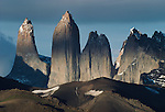 The shadow of clouds veling the snow-covered faces of these massive towers allows the pinnacles to become brighter than the lower portions, Torres del Paine National Park, Chile.